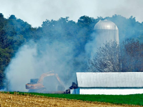 Smoke billows from the remains of a barn fire that
