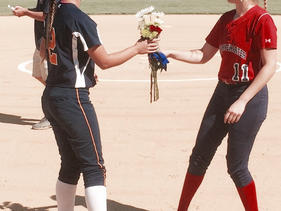 Julia Freeth, right, of Newark Charter presents flowers to Delmar's Shelby Murphy before Thursday's softball game at Folk Park in Newark.