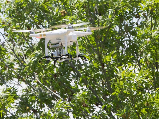 A drone piloted by Tim Lower, with the New Mexico State University Physical Science Laboratory, hovers above a grass area at the Doña Ana Community College, during a demonstration for the ACT Summer Program, Wednesday, June 13, 2018.