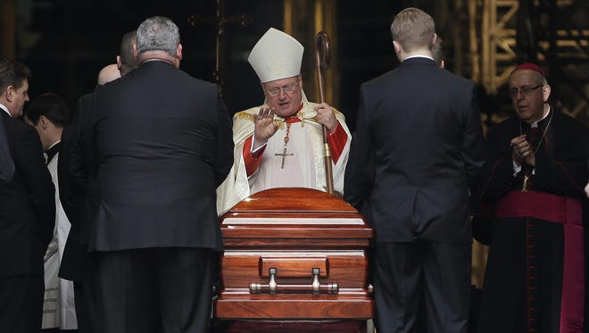 Cardinal Timothy Dolan, the current archbishop of New York, center, performs a ritual over a casket containing the body of Cardinal Edward Egan at St. Patrick's Cathedral in New York, Monday, March 9, 2015. Egan played a prominent role in New York City after the Sept. 11 terror attacks, and now New Yorkers are preparing to pay respects to the former archbishop after his death last week. (AP Photo/Seth Wenig)
