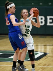 Randolph Southern's Ally Saylor moves the ball against Union City's Courtney Wise Saturday, Feb. 4, 2017, during the girls basketball sectional championship in Lynn.