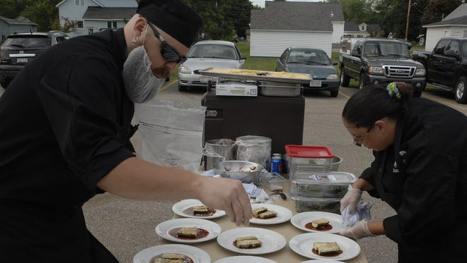Chef Scott Keller of The Canteen at Mid-State Technical College and one of his sous chefs, Tiffany Haefner, plate dishes to be served to their guests at the Iron Chef benefit for the South Wood County Humane Society in June 2014. The team won the competition.