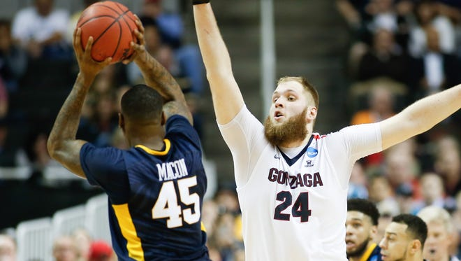 Gonzaga center Przemek Karnowski, shown defending West Virginia's Elijah Macon in the West Regional semifinals, is the key to the Bulldogs' defense.