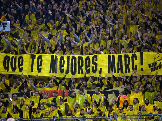 Dortmund fans hold a poster 'Get well, Marc!' during the Champions League quarterfinal first leg soccer match between Borussia Dortmund and AS Monaco in Dortmund, Germany, Wednesday, April 12, 2017. Dortmund's Marc Bartra was injured after a blast outside the Dortmund team bus the day before. (AP Photo/Martin Meissner)