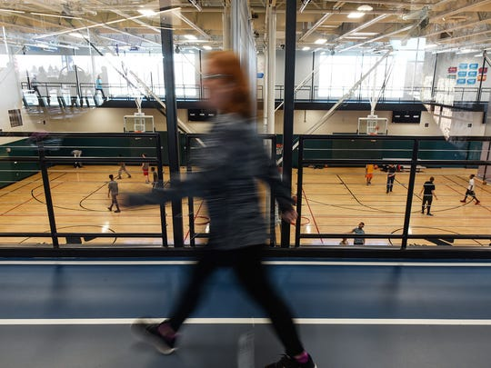 A walking tack circles the busy basketball courts as people exercise Tuesday, March 13, at the St. Cloud YMCA Community and Aquatic Center.