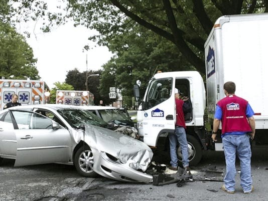 Two employees of Lowe's inspect damage to the truck they were riding in after it was struck by two cars that crashed at East Walnut and Third Avenue in Lebanon Wednesday morning.