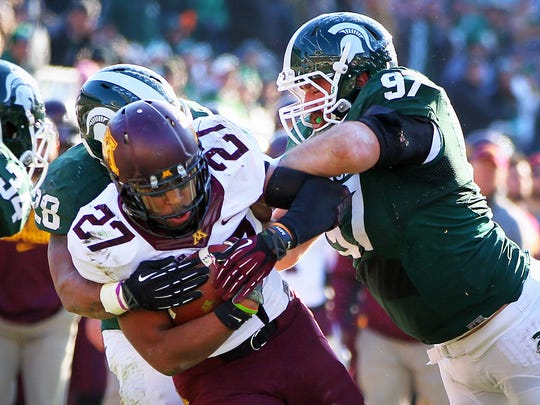 Defensive tackle Mark Scarpinato (97) tackles Minnesota running back David Cobb during the Spartans' win in 2013.