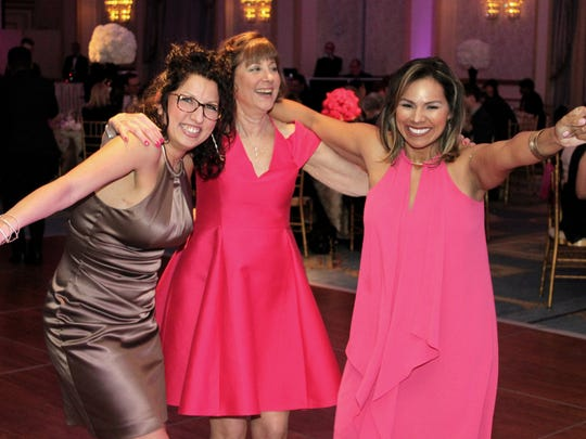 """""""Pink Sisters"""" Carrie Duane of Mount Arlington, Kathi Wolder of Scotch Plains and Ana Harper of Springfieldkick up their heels to Gloria Gaynor's """"I Will Survive"""" for the Survivor Dance, a long-standing tradition at Komen North Jersey Pink Tie events."""