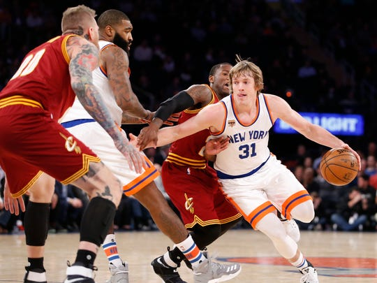 New York Knicks guard Ron Baker (31) drives around Cleveland Cavaliers guard Kay Felder, second from right, in the second half of an NBA basketball game at Madison Square Garden in New York, Wednesday, Dec. 7, 2016. The Cavaliers defeated the Knicks 126-94. New York Knicks center Kyle O'Quinn (9) backs up Baker as Cleveland Cavaliers forward Chris Andersen, far left, defends.