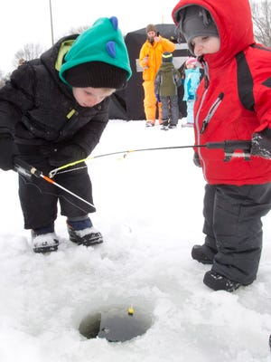 Riley Malzewski, 3, left, and his brother, Noah, 2, wait to catch a fish at McCarty Park during a free ice fishing clinic in 2014. This year's clinics, which will be held at McCarty Park and five other Milwaukee County Parks lagoons, are set for Saturday, Feb. 10.