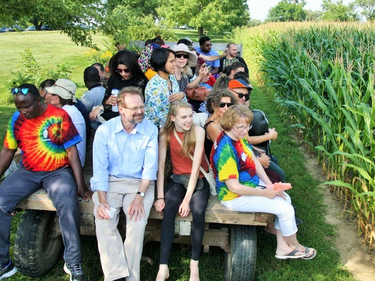 Writers from across the globe recently enjoyed a brief taste of Iowa farm life at the Dane family farm while taking part in the University of Iowa's 12-week International Writing Program. Christopher Merrill is shown in center, sitting on the back of the tractor ride.