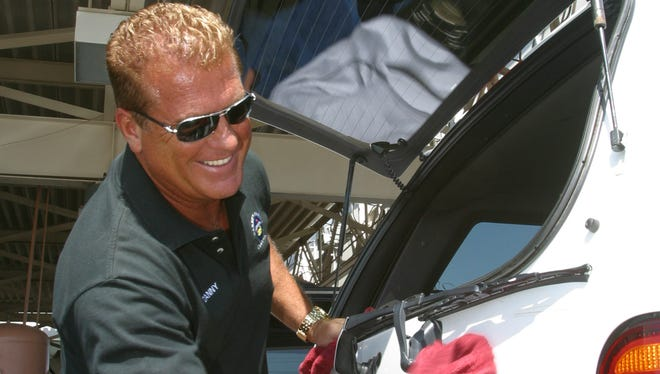 Danny Hendon, owner of Danny's Family Car Wash, helps dry cars in 2005.