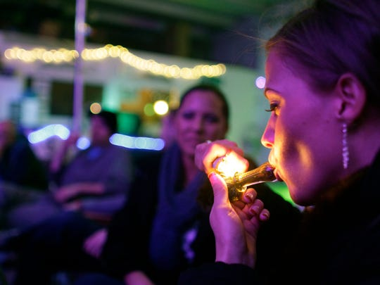 "FILE - In this Dec. 31, 2012 file photo, Rachel Schaefer, of Denver, smokes marijuana on the official opening night of Club 64, a marijuana-specific social club, where a New Year's Eve party was held in Denver. Denver is starting work on becoming the first city in the nation to allow marijuana clubs and public pot use in places like restaurants, yoga studios and art galleries. Voters narrowly approved the ""social use"" measure last November."