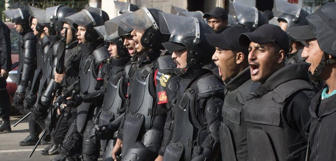 Egyptian riot policemen march toward Cairo University on March 19, 2014, as clashes broke out during a protest by Muslim brotherhood students, supporters of ousted President Mohammed Morsi.