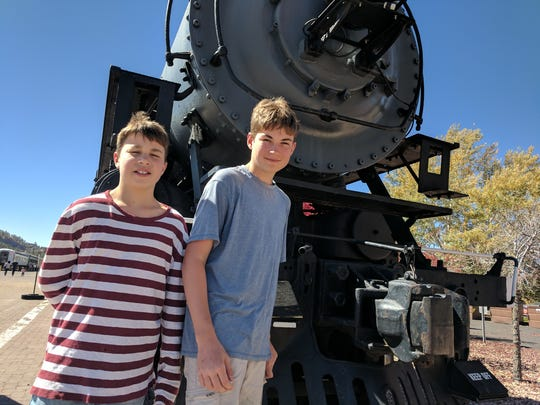 Aren and Iden Elliott check out a train in Williams,