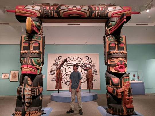 Aren Elliott inspects a Native American carving at