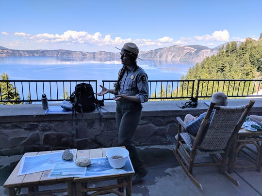 With dramatic Crater Lake in the background, a park ranger gives a talk on how the lake was formed. She is speaking from the verandah of the Crater Lake Lodge.