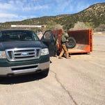AmeriCorps volunteers unload scrap tires at Mescalero Tribal Store parking lot.