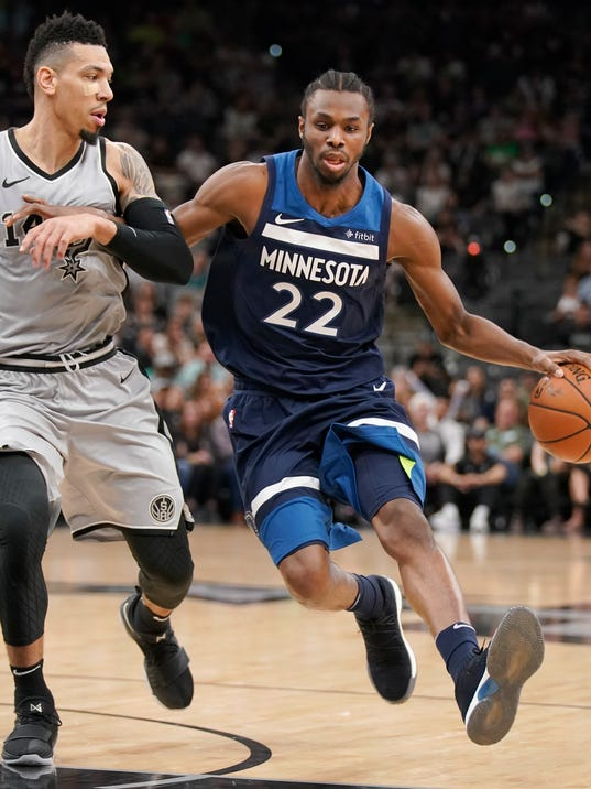 Minnesota Timberwolves' Andrew Wiggins (22) drives against San Antonio Spurs' Danny Green during the first half of an NBA basketball game, Saturday, March 17, 2018, in San Antonio. (AP Photo/Darren Abate)