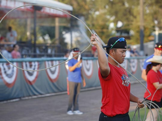 Visalia Rawhide's Bo Takahashi tries his hand at roping at the Cal League All-Star Fan Fest at Rawhide Stadium Monday, June 19, 2017 in Visalia, Calif. This year the events included the In-N-Out Burger High School Hitting Challenge, an All-Star Skills Challenge, which included the Cow Milking Contest, and culminated with a Home Run Derby.