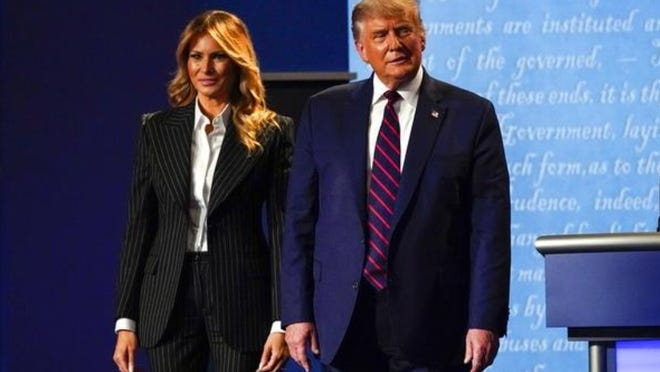 President Donald Trump stands on stage with first lady Melania Trump after the first presidential debate Tuesday in Cleveland. President Donald Trump and first lady Melania Trump tested positive for the coronavirus, the president tweeted early Friday.