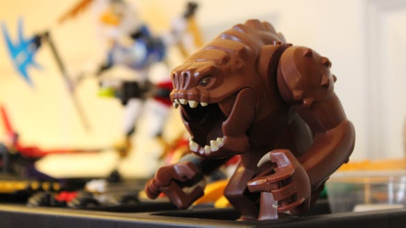 The Rancor keeps watch with the other Lego creations.