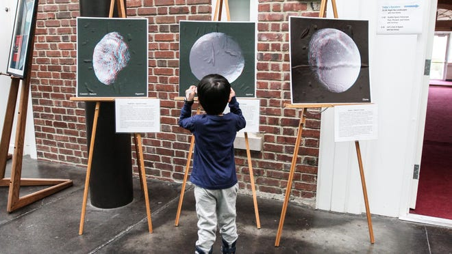 Russell Montgomery, 3, looks at pictures of the moon with 3D glasses during Astronomy Day on Saturday.