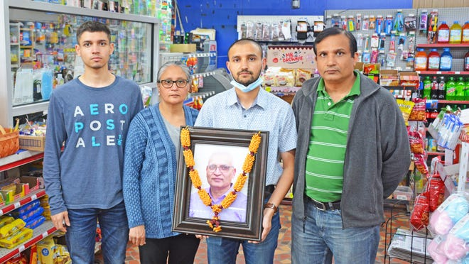 The family of Andy Patel holds his photo inside the Corner Stop convenience store, which has reopened after being closed for two weeks following Andy's murder. Pictured are Andy's son Krusang, wife Panna, son Mahir and brother Piyush.