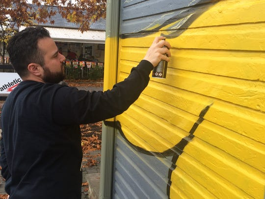 "Street artist JC Rivera is shown painting his signature brand, ""The Bear Champ,"" on a building in Broad Ripple on Saturday, Oct. 24, 2015."