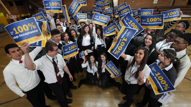 The senior class at Cristo Rey High School in Detroit wave their college acceptance banners on Thursday, Jan. 15, 2015.