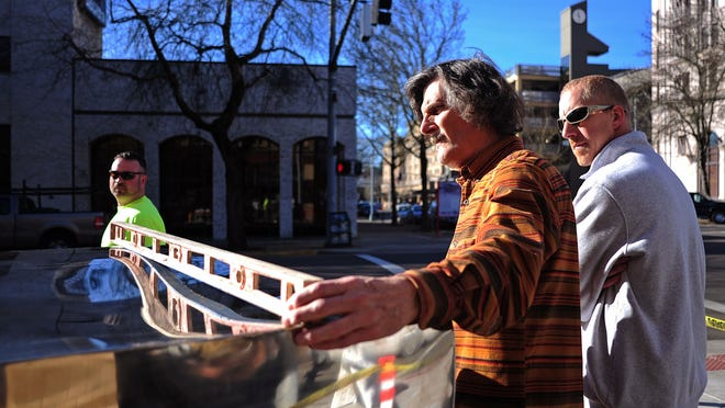 """Steven Addams checks to see if """"Untitled (Cube)"""" is level at its new location at the northeast corner of State and Liberty streets."""