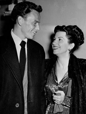 Singer Frank Sinatra and his wife Nancy smile broadly as they leave a Hollywood nightclub following a surprise meeting.