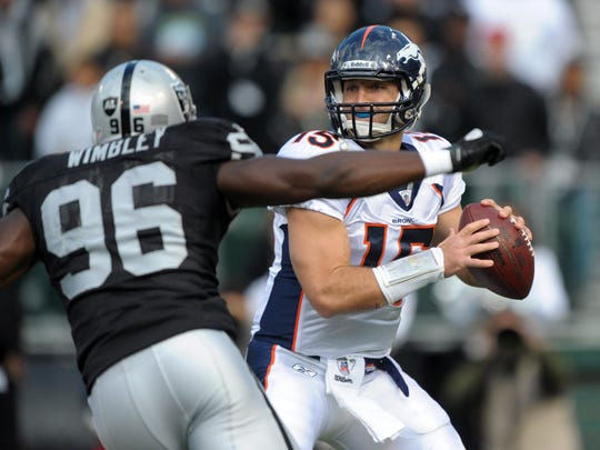 Denver Broncos quarterback Tim Tebow (15) is pressured by Oakland Raiders linebacker Kamerion Wimbley (96) in 2011.