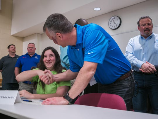 Samantha Pearlman, of St. Georges Technical High School, signs with Nickle Electrical Companies as thirteen high school seniors representing all four NCC Vo-Tech high schools join representatives from companies that have offered them jobs upon graduation.