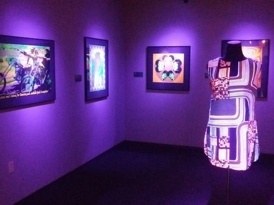 Posters and a dress are featured in the black light