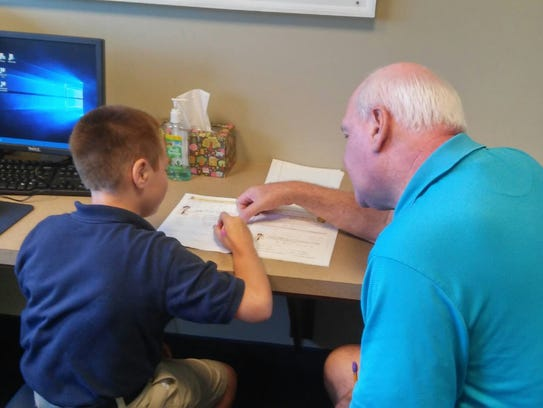 Ken Palmer helps Aiden with is lessons at the Samaritan