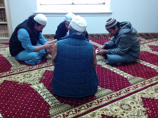 Attendees of the Islamic Organization of the Southern Tier sit on a prayer carpet in the women's sanctuary at the mosque.