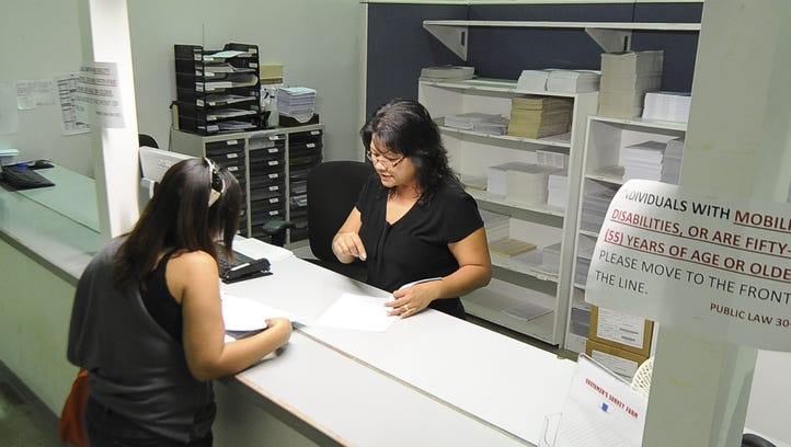 Income Tax Specialist Jerrilynn Asuncion, right, assists a customer at the Department of Revenue and Taxation in Barrigada Heights in March 2012.
