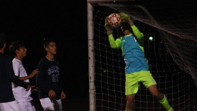 Salem goal-keeper Karson Gregory squeezes a hard shot from Plymouth Wednesday night.