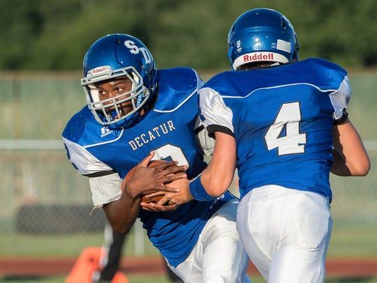 Decatur quarterback Dominic Klebe (4) hands the ball