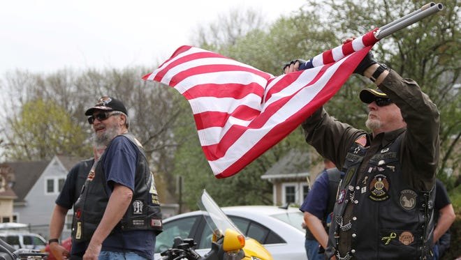 Army Veteran Mike Johnson, of Ankeny, a member of the patriot guard and Marshalltown American Legion wraps up an American flag after the funeral for Navy Veteran Charles Lanam on Monday, April 18, 2016, at the Iowa Veterans Home Cemetery in Marshalltown.