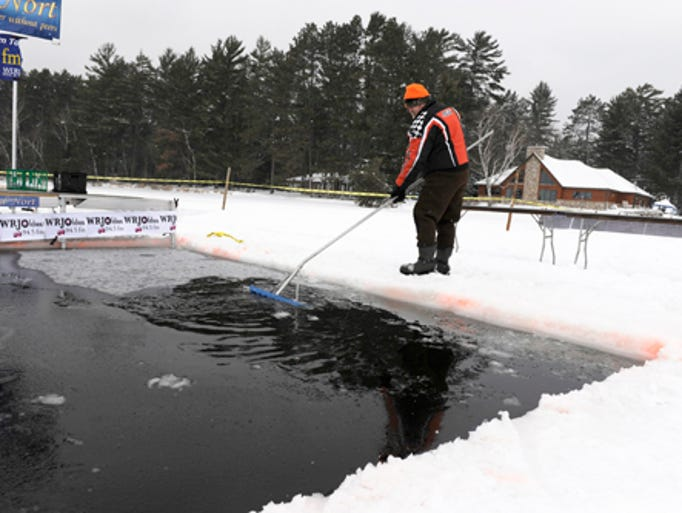 George Schroeder of St. Germain skims ice off the water as he waits for the start of the 14th annual Northwoods Original Polar Bear Plunge on Saturday. He and a few other men cut a hole measuring 14? by 18? to accommodate the polar bear participants. The ice was 15 inches thick, he said. Eight-two people took the plunge into the ice waters Saturday, Jan. 4 at the Polar Bear Plunge to benefit the Angel on My Shoulder charity. The pledges and raffle ticket sales should tally over $26,000, according to a spokesperson for the event, which was held on Big St. Germain Lake with headquarters at Fibber?s Bar and Restaurant.