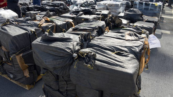 This photo provided by the U.S. Coast Guard, a crewman from the Coast Guard Cutter Boutwell shows some of more than 28,000 pounds of cocaine, seized at sea and offloaded at Naval Base San Diego Thursday, April 16, 2015. The vessel arrived with more than 14 tons of cocaine, part of what authorities described as a surge of seizures near Central and South America. (U.S. Coast Guard photo by Petty Officer 1st Class Henry G. Dunphy via AP) MANDATORY CREDIT