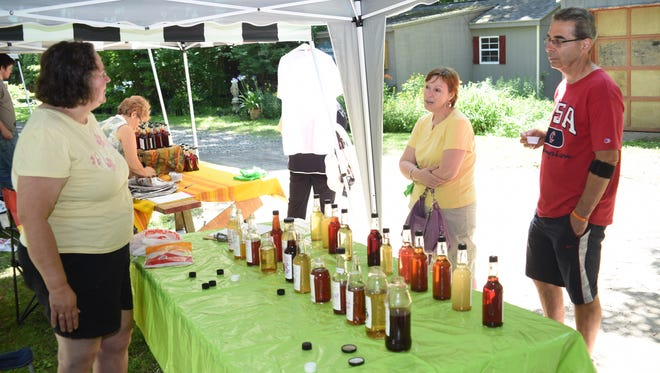 Volunteer Ann Shershin explains the different flavor vinegars to Johnna and Miek Touma from Pleasant Valley during the 8th Monestary Vinegar Festival  held at the Our Lady of the Resurrection Monastery in Lagrangeville on Saturday.