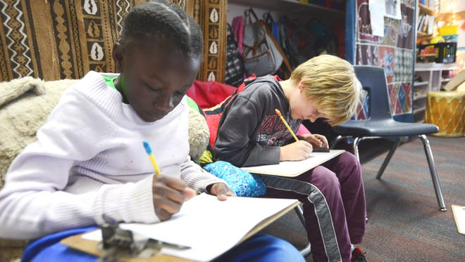 Integrated Arts Academy fourth-graders Johali Yapemacho and Robin Hokenmaier  prepare their entries for a contest sponsored by the Burlington Electric Department.