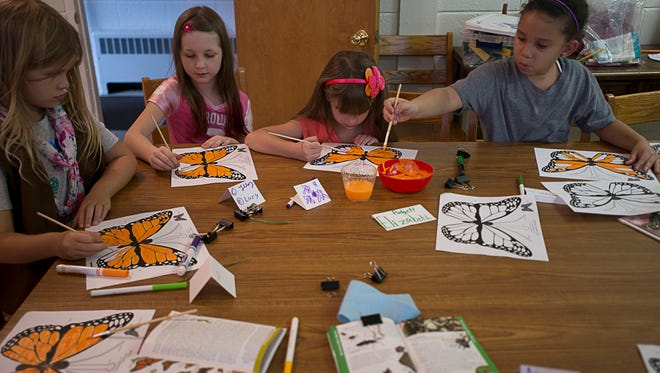 Black Mountain Girl Scout Brownies paint pictures of a Monarch butterfly Tuesday October 6, 2015 at the Black Mountain United Methodist Church.