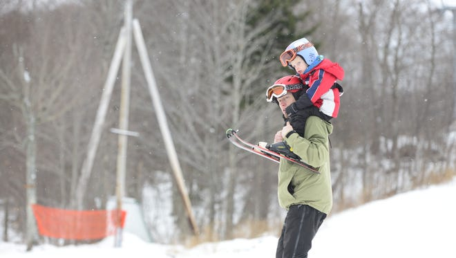 Kristian Omland of Jericho carries his son Aron, 2, on his shoulders during a family ski visit to Bolton Valley Resort on Saturday, Jan. 2, 2016.