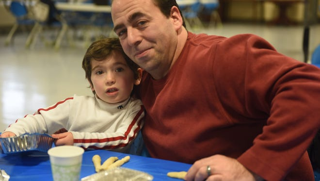 Lee Posniack (right) and his son, Seth, worked together to braid Challah bread at the Fishkill Recreational Center, 793 Route 52, Sunday. The event, aimed at bringing families together and teaching them about traditions in the Jewish faith, was hosted by the Pardess Center for Jewish Life in South Dutchess.