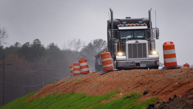 Motorists on Lakeland Drive in Floowood skirt a steep enmankment as they travel east through a construciton zone where a project to widen the roadway has begun.