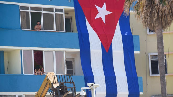Workers unload equipment on the street outside the U.S. Embassy in Havana, Cuba, as residents of an apartment building watch the preparations prior to the Aug. 14, 2015, flag raising at the U.S. Embassy.